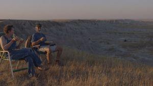 Vern och Dave sittande i solstolar framför ett öpped,öde landskap.