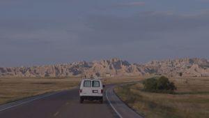 en ensam bil kör mot ett öppet landskap med berg i bakgrunden.
