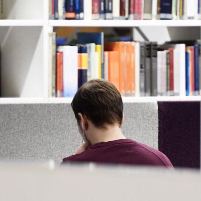 En studerande i Helsingfors universitets huvudbibliotek sitter med hörlurar i öronen och med ryggen vänd mot kameran.