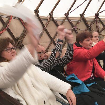 Kulttuuri-innostajat Satu Nokkonen, Anne Lahtinen ja Jenny Palomäki osallistuivat lauluhetkeen Keinupuistokeskuksen pihalle pystytetyssä jurtassa. Mukana myös keskusken asukas Raimo Ahola.