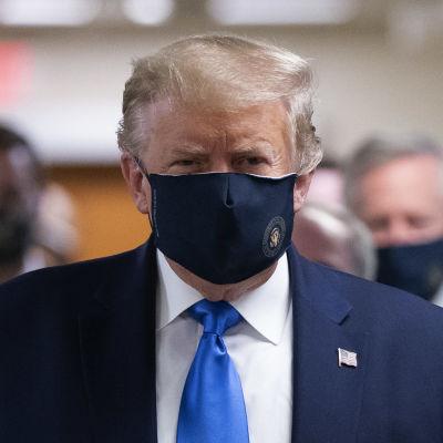 Donald Trump i ansiktsskydd. Bakom honom syns fler personer bära mask.