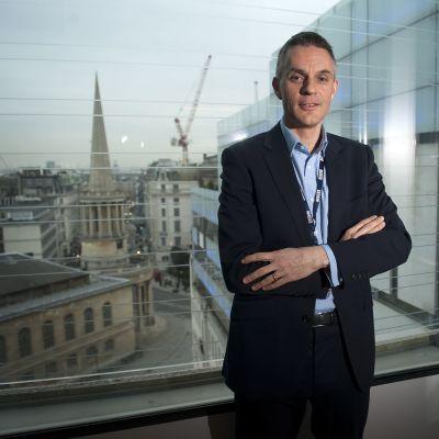 Tim Davie poseeraa kuvassa taustallaan Lontoon rakennuksia.
