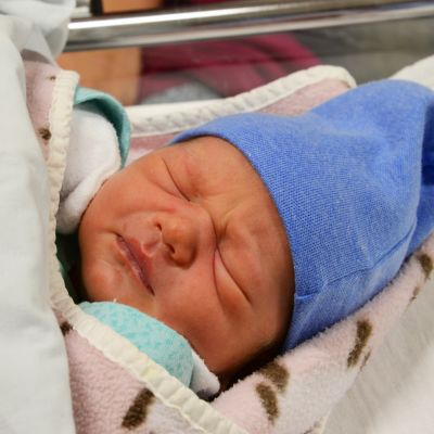 kahden päivän ikäinen poikavauva nukkuu sininen pipo päässä