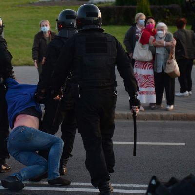 Poliisit raahasivat mielenosoitukseen osallistunutta miestä keskiviikkona pääkaupungissa Minskissa.