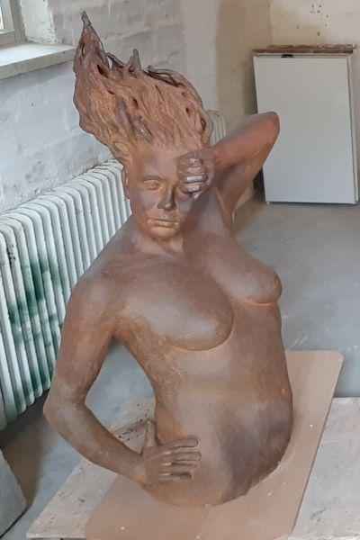 Tre skulpturer i bränd lera, två kvinnor och ett barn, i ett ljust garage, väntar på att placeras som utomhuskonst.