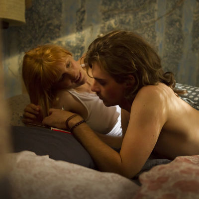 Inak och Juhana ligger tätt intill varandra på en säng, han skriver och hon tittar på honom.