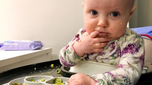 en ettåring äter broccoli med egna händer