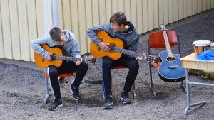 Två pojkar sitter utomhus och spelar gitarr.