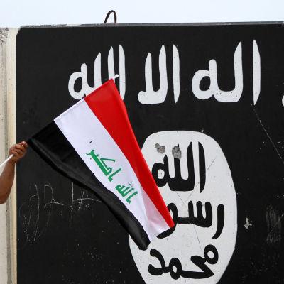 En hand som håller i Iraks flagga framför en svartvit IS flagga.
