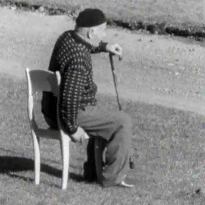 Vanha mies istuutuu tuolille ulkona