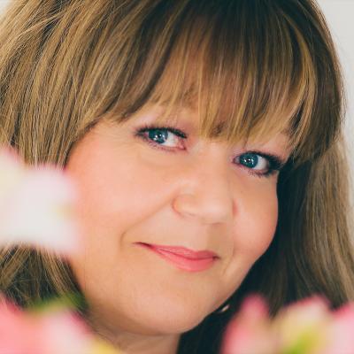 En kvinnas ansikte med blommor i förgrunden.