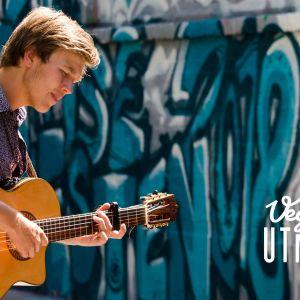Erik Sjøholm med sin gitarr framför en vägg.