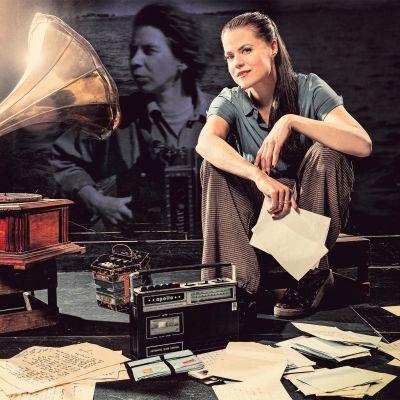 En ung kvinna sitter på en låg pall bredvid en gammal grammofonspelare. I bakgrunden skymtar ett svartvitt foto av Tove Jansson. På golvet ligger gamla papper kringströdda.