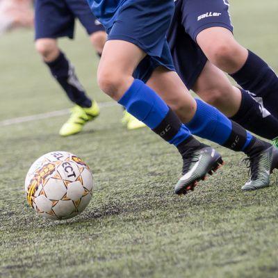 Lapsia pelaa jalkapalloa.