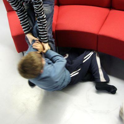 Lapset tappelevat latttialla.