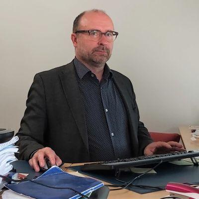 Pasi Leimi on työpöytänsä äärellä.