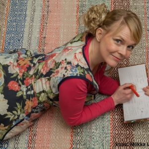 Heli Laaksonen makaa lattialla ja tekee muistiinpanoja.