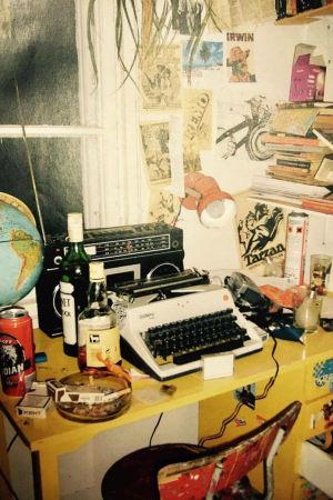 Skrivbord, skrivmaskin, flaskor och fimpar