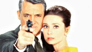 Cary Grant (ase kädessä) ja Audrey Hepburn poseeraavat Charade-elokuvan mainoskuvassa.