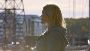 Nainen seisoo ja katsoo utuiseen kaupunkimaisemaan