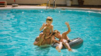 Paul med sina två små barn i en bassäng med turkost vatten. Ena barnet sitter i en simring och det andra på Pauls axlar.