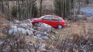 En liten röd bil med framändan på en stenhög. Bilen är lite tillknycklad framtill och har ett gult plastband om sig.