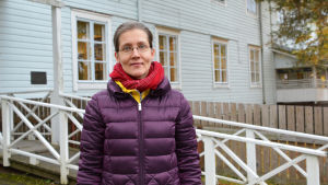 En kvinna i lila jacka står utanför ett blått trähus. Kvinnan tittar in i kameran.