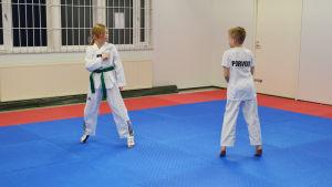 Två barn i vita dräkter står mitt emot varandra. Det ser ut som om de ska påbörja en taekwondomatch. De står i en idrottssall med rödblå gummimatta på golvet.