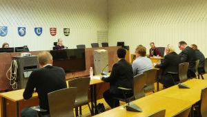 Sex personer sitter på rad i en rättegångssal framför en domare, åklagare och ett rättegångsbiträde.