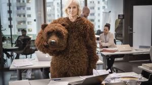 Lyhytelokuvan pääosanainen pukeutuneena karhupukuun, karhun pääosa kainalossa.