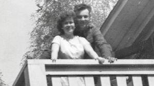 En gammal svartvit bild av en kvinna och en man som står nära varandra på en balkong och tittar in i kameran.