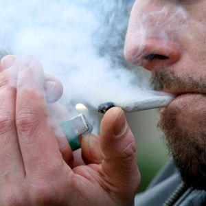 man tänder en cannabiscigarett.