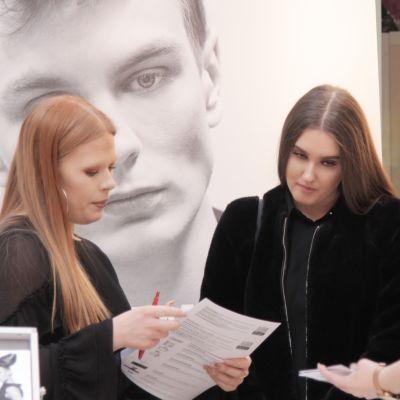 Kolme tyttöä täyttää papereita koekuvaukseen pääsemiseksi