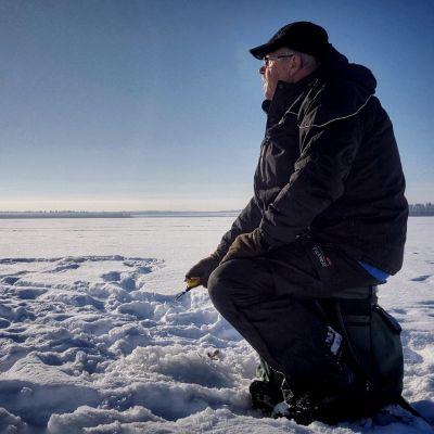 Rauno Veteläinen pilkkii Kuusamojärvellä.