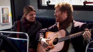 Mies (Glen Hansard) soittaa kitaraa naiselle (Markéta Irglová) bussin penkillä. Kuva elokuvasta Once.