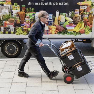Ruokalähetti työntää ostoksia nokkakärryillä Tukholmassa.