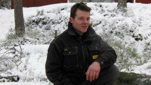 Daniel Eriksson sitter vid en grillplats utsomhus på vintern