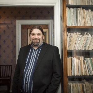 En leende man står framför bokhylla