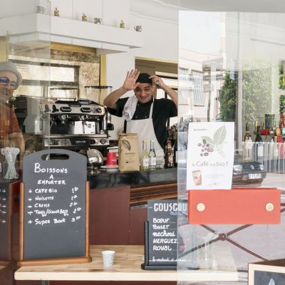 Kuvassa on pariisilainen Le Stendhal -kahvila. Työntekijä vilkuttaa sisältä ulos.