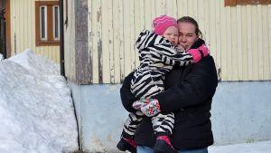 Porträttfoto av kvinna med barn i famnen. Kvinnan har svart jacka, mörkt hår och blå jeans. Barnet är 2,5 år gammalt och har en zebrarandig overall samt en rosa mössa. I bakgrunden syns ett hus och snö.