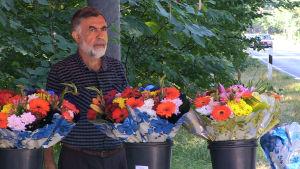 Ali Toy säljer blommor på den plats där hans chef mördades.
