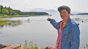 En kvinna står och pekat mot en punkt ute på vattnet i en vik.