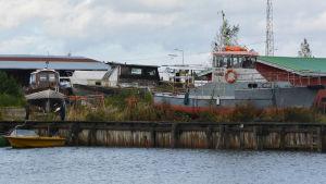 På bilden syns båtar på land. Vissa av dem ser inte ut att vara i bra skick.