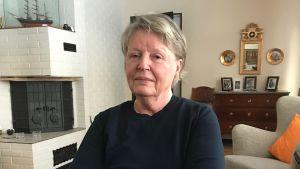 En svartklädd kvinna sitter i ett vardagsrum