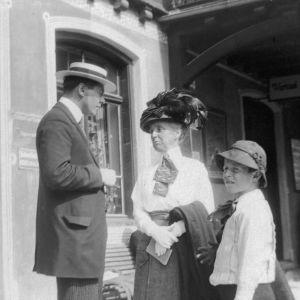 Äldre kvinna, ynre man och pojke på perrong vid järnvägsstation. Edith Södergrans samling