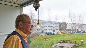Äldre man tittar ut genom fönster.