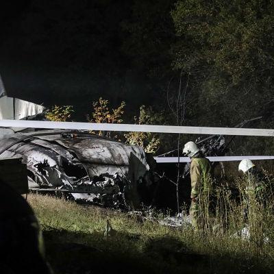 Två personer i hjälm och räddningsoverall står bredvid ett totalförstört flygplan.