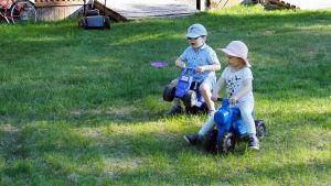 Lapset leikkivät kesäisellä nurmella.