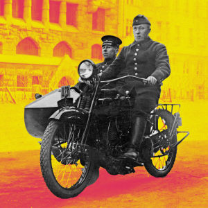 Palomies ja ruiskumestari ajavat Helsingin palolaitoksen sivuvaunullisella Harley-Davidson-moottoripyörän 1920-luvulla. Taustalla alipäällystön lapsia.