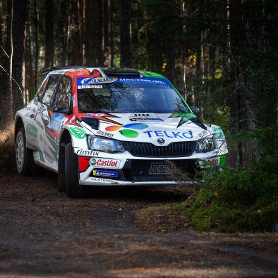 En rallybil svänger i hård fart på en skogsväg.